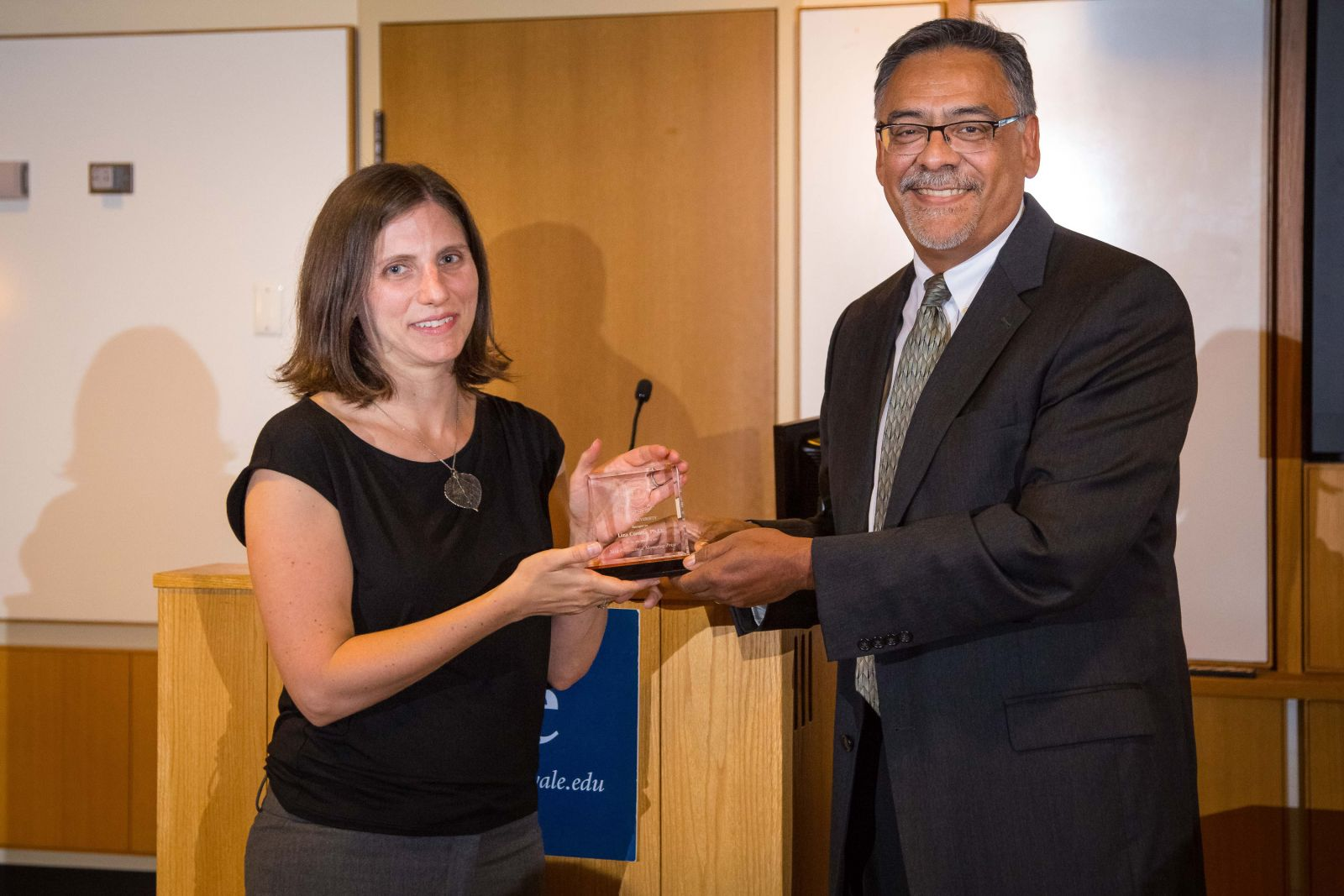 Rick Bribiescas, Deputy Provost for Faculty Development and Diversity, presents the 2016 Mentor of the Year plaque to Liza Comita, Assistant Professor of Forestry and Environmental Studies.